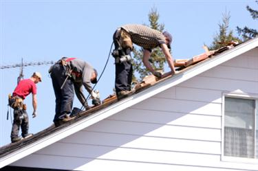 Roof Installation in Spring Lake Park MN. Three roofers laying new shingle on a roof in Spring Lake Park.